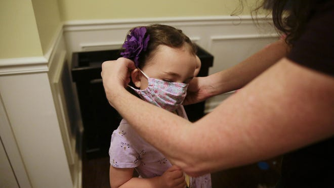 A mother helps her 5-year-old daughter  put on her mask before her first day of kindergarten on Aug. 3 in Dallas, Ga.