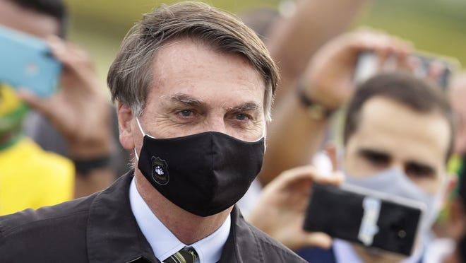 FILE - In this May 25, 2020, file photo, Brazil's President Jair Bolsonaro, wearing a face mask amid the coronavirus pandemic, stands among supporters as he leaves his official residence of Alvorada palace in Brasilia, Brazil. Bolsonaro said Tuesday, July 7, he tested positive for COVID-19 after months of downplaying the virus's severity while deaths mounted rapidly inside the country.