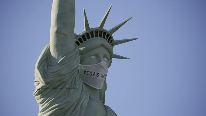 An oversized mask adorns the face of a replica Statue of Liberty at the New York-New York hotel and casino Thursday, July 16, 2020, in Las Vegas. MGM Resorts International has put a mask on the Statue of Liberty to remind people to wear a face covering as a precaution against coronavirus.