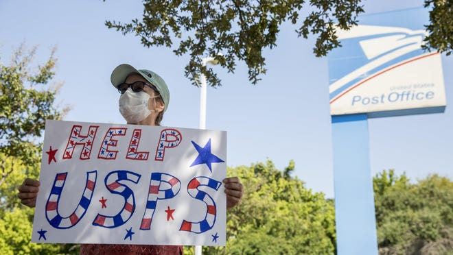Sarah Lyford holds a sign in support of the United States Postal Service during a rally located in front of Post Office in North Austin on August 18, 2020. The Trump administration aims to implement changes to the Postal Service ahead of the November election. President Trump said that he opposed additional funds for USPS, even though the money would be needed to manage mailed-in ballots in the fall election from voters seeking to avoid crowds in polling placed amid the coronavirus pandemic.