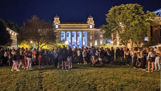Students gathering on the Syracuse University campus on Wednesday Aug. 19, 2020, in Syracuse, NY. Syracuse University has issued suspensions to 23 students in the wake of the large on-campus gathering that administrators say could force them to shut down campus. College officials announced the disciplinary action late Thursday, Aug. 21, 2020.
