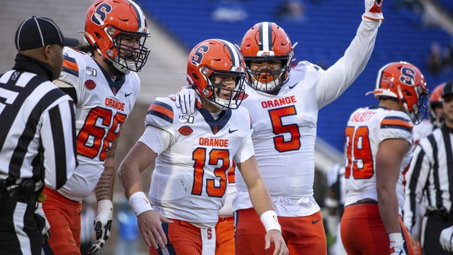 Syracuse's Tommy DeVito (13) celebrates with Chris Elmore (5) and Airon Servais (68) after a play during a game last season. The Syracuse Orange have missed a few practices because of concerns about COVID-19 safety protocols, but the players so far have publicly exhibited a dose of solidarity about playing during the coronavirus pandemic.