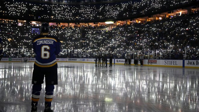 In this Dec. 1, 2017, file photo, St. Louis Blues' Joel Edmundson pauses as fans use their phones to light up Scottrade Center during a ceremony as part of a league-wide cancer awareness campaign, before an NHL hockey game in St. Louis.