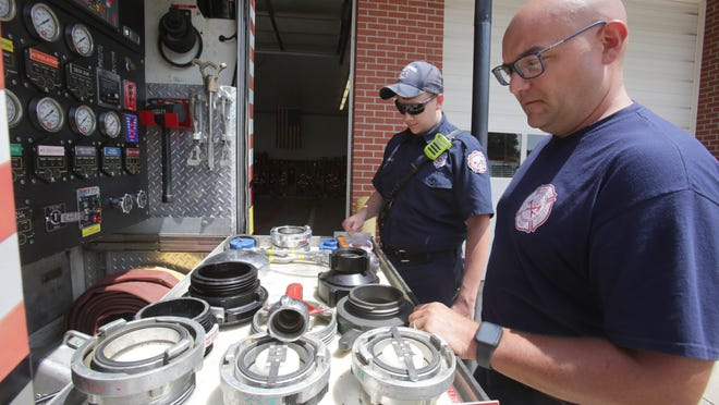 North Lawrence firefighter Nathan Cunningham inspects a pumper truck with Chief Jason Rock (right).
