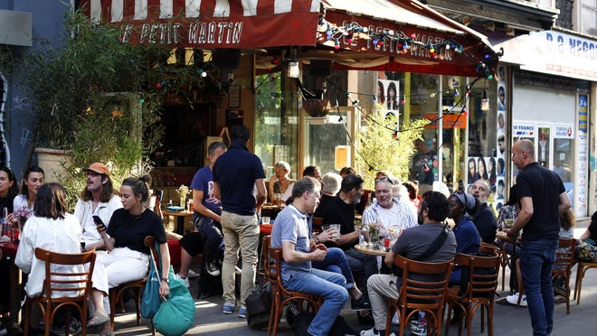 People sit on the terrace of a cafe in Paris, Tuesday, June 2, 2020. Paris City Hall authorized the reopening of outside seating areas but indoor tables remain closed to customers until at least June 22.