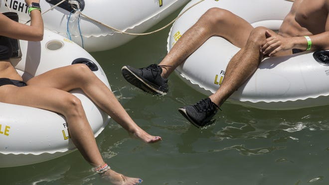 The feet of Julia Ortega and Christian Casis float in the San Marcos River on Monday, July 8, 2019.