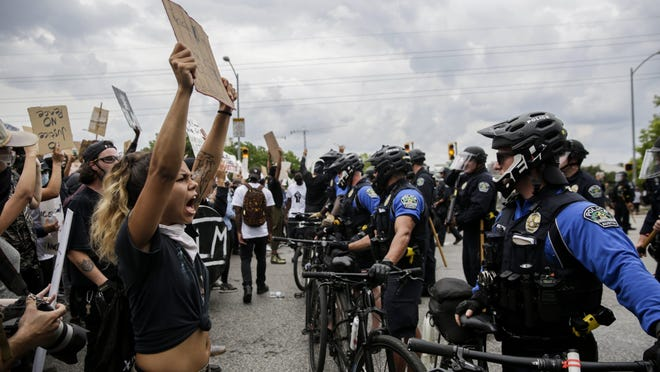 People gather by the thousands in protest of the killings of George Floyd and Michael Ramos as Austin police block their path Sunday. Large gatherings of people without masks in close quarters could increase the spread of the coronavirus.