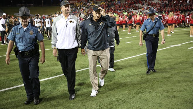 Chad Moller, left center, walks next to former Missouri head football coach Gary Pinkel, center, after a game against Arkansas State on Sept. 12, 2015, at Centennial Bank Stadium in Jonesboro, Ark.