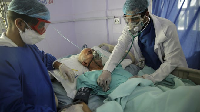 Medical workers attend a patient in an intensive care unit at a hospital for the coronavirus disease COVID-19 in Sanaa, Yemen, Sunday, Jun. 14, 2020.