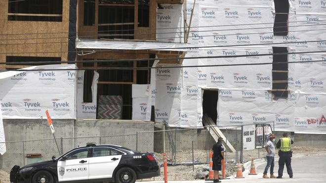 Austin police officers investigate where a construction worker fell four stories at a construction site in the 2500 block of Montopolis Drive in Southeast Austin on Friday.