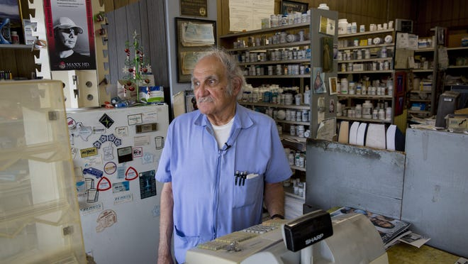 Pharmacist José Gutierrez, 80, stands behind the cash register in his Neighborhood Pharmacy on East Seventh Street. He filled prescriptions there and at another nearby pharmacy for a total of 58 years.