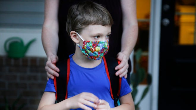 Rachel Adamus holds her son Paul, 7, on their porch before the bus arrives for the first day of school on Monday, Aug. 3, 2020, in Dallas, Ga. The Adamus children are among tens of thousands of students in Georgia and across the nation who were set to resume in-person school Monday for the first time since March.