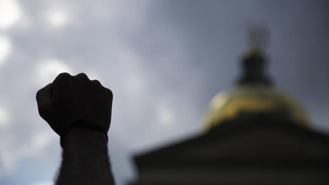 A person holds up a fist near the Georgia State capitol during a protest on Monday, June 15, 2020, in Atlanta.