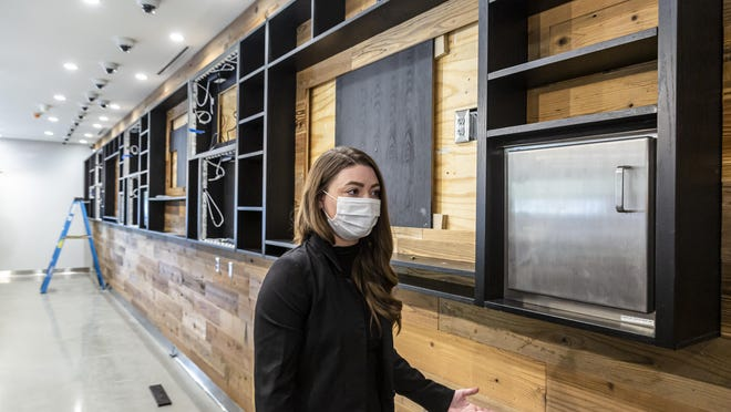Emma Ross, the general manager of the new Ascend Cannabis Dispensary on Horizon Drive, demonstrates the cabinet that is used as a secure pass through for cannabis products from the dispensary's vault to the budtenders that will be servicing customers during a tour of the new facility under construction, Thursday, Oct. 15, 2020, in Springfield. The secure pass through can only be opened from one side at a time and was built as not only a more efficient service for the customer, but also for safety with COVID-19 pandemic in mind.