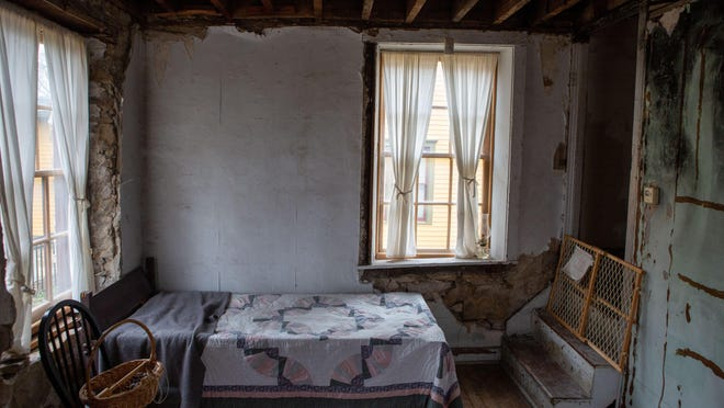 Inside a room of the Ritchie House, a bed is made to show how the room could have been set up back in the day.