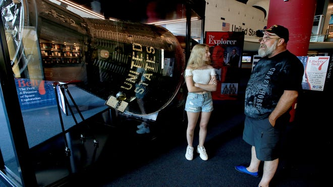 Joe Combs, from Wichita, right, looks at the Liberty Bell 7 capsule with his daughter, Elizabeth Combs, 15, as she reads the signs about the spacecraft Tuesday in the lobby of the Cosmosphere, 1100 North Plum.