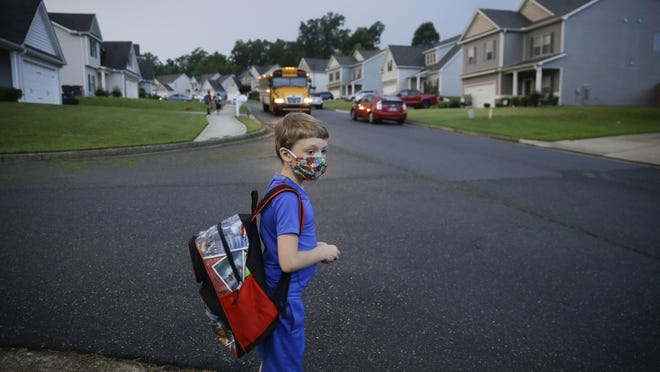Paul Adams, 7, waits at the bus stop for the first day of school on Monday, Aug. 3, 2020, in Dallas, Ga. Neighboring states arrived at differing conclusions on who's in charge of the reopening of schools. The differences in philosophy underscore some of the difficulties facing states as they grapple with how to proceed amid growing coronavirus infections in numerous states.