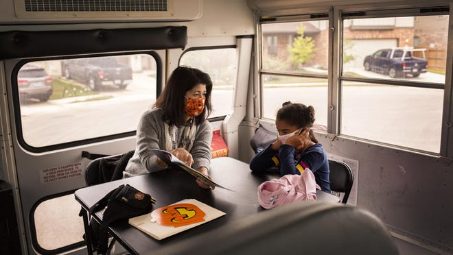 Lou Quinlan, the lead assessor for the Hutto school district's special education program, reads to Michaela Weeks, 7, while on a school bus outside Michaela's home. The bus was provided by the school district to offer in-person learning to students with different needs during the coronavirus pandemic.