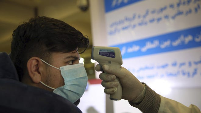 An Afghan health worker takes the temperature of a passenger as a preventive measure for coronavirus during screening of travelers who arrived from China, at the Hamid Karzai International Airport in Kabul, Afghanistan, in February.