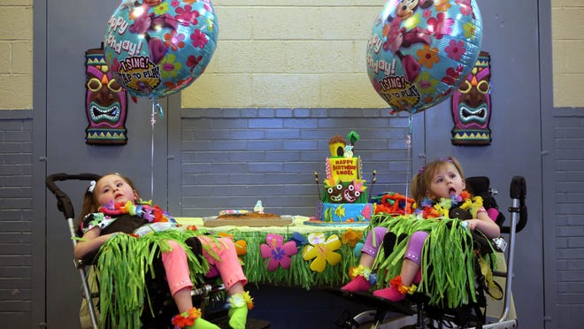 Layla and Angel Martin celebrate their fourth and third birthday in South Lebanon surrounded by family and friends Saturday, March 28, 2015. Each girl has a rare inherited genetic disease called infantile neuroaxonal dystrophy, which causes paralysis and pain.