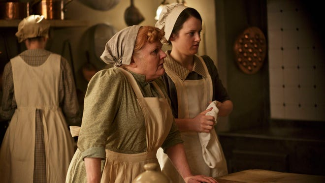"""This photo released by PBS and Carnival Film and Television Limited shows, from left, Lesley Nicol as Mrs. Patmore, and Sophie McShera as Daisy, in a scene from season four of the Masterpiece TV series, """"Downton Abbey."""""""