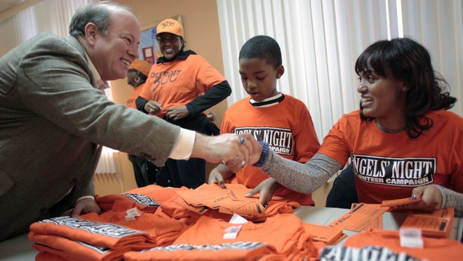 Mayor Mike Duggan, left, shakes hands with Cherie Polk, right, from Detroit, as she organizes cards and shirts at the Life Builders building on Saturday, Oct. 11, 2014 in Detroit.