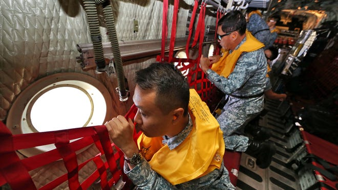 Republic of Singapore Air Force personnel aboard a C130 aircraft participate Monday in the search operation for missing AirAsia flight QZ8501 at sea.