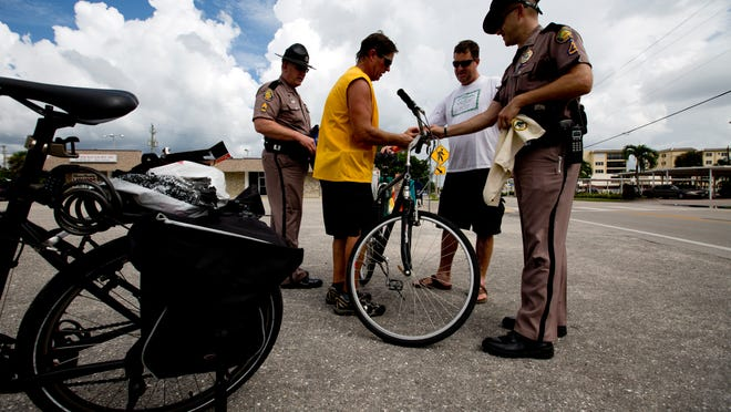 Dan Moser, center left, an EMS injury prevention outreach worker, attaches a light to Fort Myers Beach resident John Luttrell's bike with the help of Florida Highway Patrol trooper.