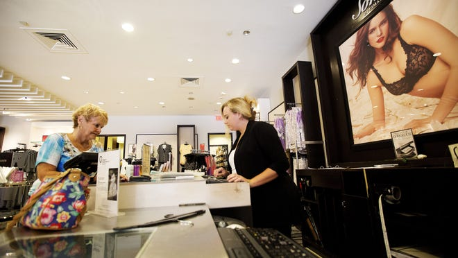 Samantha Incardona, center, a manager at Soma at the Bell Tower Shops, checks out customer Diane Baker in 2014.