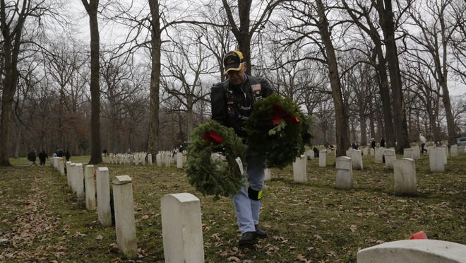 Howard Koehl, a member of the Indiana Patriot Guard, lays a wreath on the grave marker of a veteran Saturday at the Indiana Veterans Home. About 100 people turned out Saturday to participate in the local effort tied to Wreaths Across America. Each year, wreaths are placed at more than 750 national cemeteries and veteran monuments for National Wreaths Across America Day. Locally, 1,800 wreaths were laid at the veterans home.