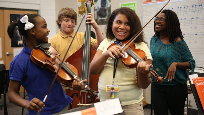 Valley High Prep students, from left, Derrica Glass, Matthew Staton, and Jamiah Roberson have a laugh during instructor Cordia Thompkins' orchestra class.