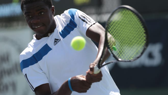 Francis Tiafoe hits a backhand return to Nathan Ponwith during the boys' 18s championship at the Easter Bowl tournament Sunday at the Indian Wells Tennis Garden. Tiafoe won 7-6, 3-6, 6-2.
