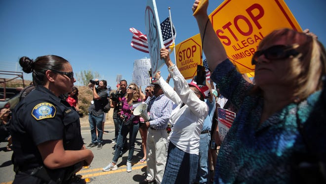 Protesters block three buses carrying illegal immigrants, arrested in Texas, from entering a US Border Patrol Station in Murrieta on Tuesday, July 1, 2014.