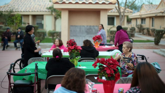 Residents at Desert Garden Apartments in Indio enjoy a free meal during Coachella Valley Housing Coalition's Christmas giveaway event on Friday, December 19, 2014 at the. Children and seniors at the apartment complex received gifts.