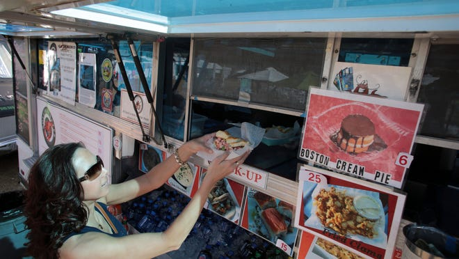 Kate Poknis, of Pittsburg, gets an order of lobster roll, lobster sliders and fries from the Roll'n Lobster food truck at the Humana Challenge on Thursday in La Quinta. The line at the food truck was long, with golf fans looking for authentic East Coast seafood.