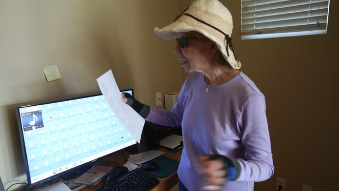 Molly-Ann Leiken, a song writer, recently was hacked and claims that her website is now unusable and hence has lost thousands of dollars in revenue. In this photo Leiken looks over a new written song she has just completed.