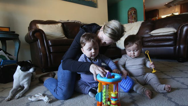 Tricia Casella, a new mother in Bermuda Dunes, plays with her twin sons, Lucca. left, and Enzo, right. At only 10 months old, the twins are too young to be vaccinated against the ongoing measles outbreak.