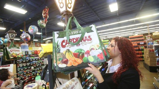 Cardenas Market supervisor Marisela Vazquez gets a reusable bag for a customer.