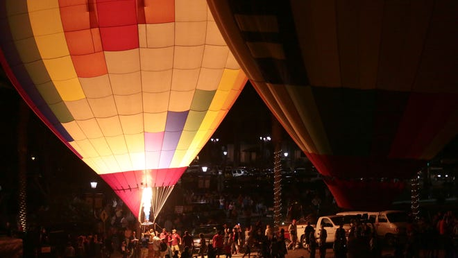 Crowds in from of the Cathedral City Hall gather around the hot flames of about a dozen balloons during the City's Hot Air Balloon Festival.