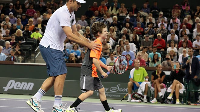 Andy Roddick partners with Jagger Leach, 7, for a few points at the BNP Paribas Challenge and The McEnroe Challenge for Charity presented by Masimo event at Stadium 2 at the Indian Wells Tennis Garden on Saturday.