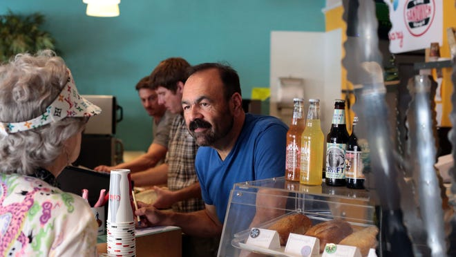 Corey Saldana the owner of The Sandwich Spot in downtown Palm Springs takes a customer's order on Friday.