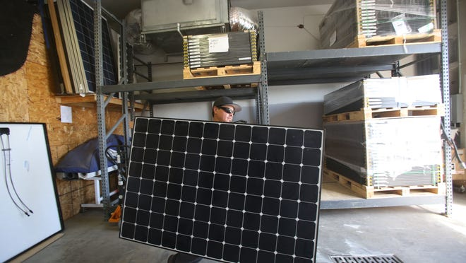 Hot Purple Energy crew installer Nick Hernandez arranges panels at the Palm Springs warehouse.