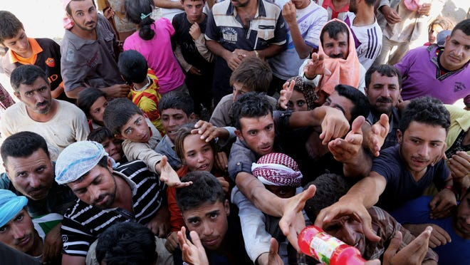 Displaced Iraqis from the Yazidi community gather for humanitarian aid at the Iraq-Syria border at Feeshkhabour border point. Kurdish authorities at the border believe some 45,000 Yazidis passed the river crossing in the past week and thousands more are still stranded in the mountains.