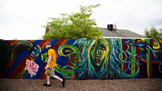 Peoria resident Vincent Rogers, 23, whose artist name is Arthur Owsley, was invited to paint a mural on a backyard wall. He used bright, vivid colors in his images, which included flowers to represent the homeowner's grandchildren.