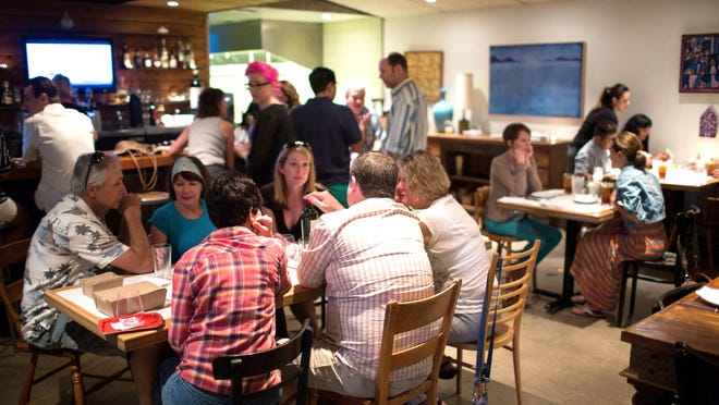 Customers enjoy food and drinks in the dining room at Tuck Shop on Saturday in Phoenix's Coronado neighborhood. Selling tickets has virtually eliminated no-show diners at the restaurant, owner DJ Fernandes says. <252,1>