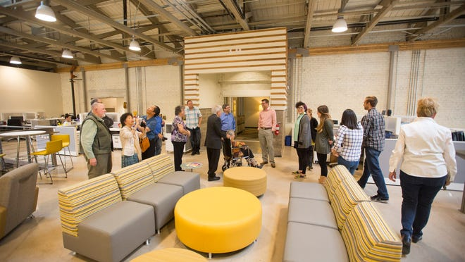 Visitors tour R&R Partners' new Phoenix office. The marketing and communications agency purchased a former grocery-store warehouse south of downtown Phoenix and hung on to the building during the recession. Major renovations included the brick walls and roof trusses.
