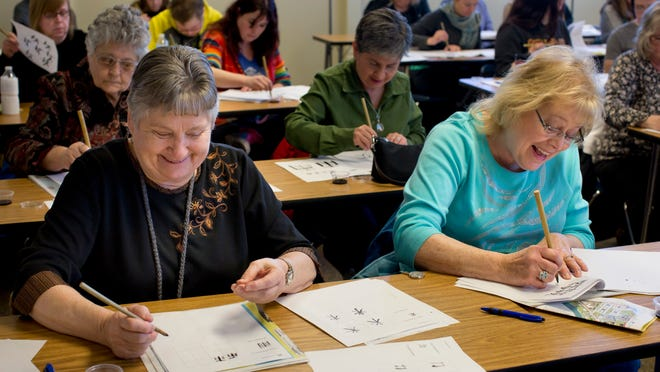 Geraldine Sedich, of Goodells, and Vicki Morse, of St. Clair, practice writing characters while taking a Japanese calligraphy class during Free College Day Saturday at St. Clair County Community College.