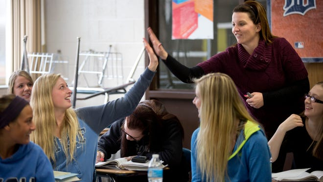 Teacher Lisa Burns gives senior Katie Kracht, 18, a high-five during an AP statistics class Tuesday, March 31, 2015 at Algonac High School. The Algonac Board of Education approved lowering the credit requirement to graduate, from 23.5 to 22 credits. Principal Ryan Melrose hopes the change will encourage students to take more challenging classes without having to worry about credits, and help students who struggle in their freshman and sophomore years.