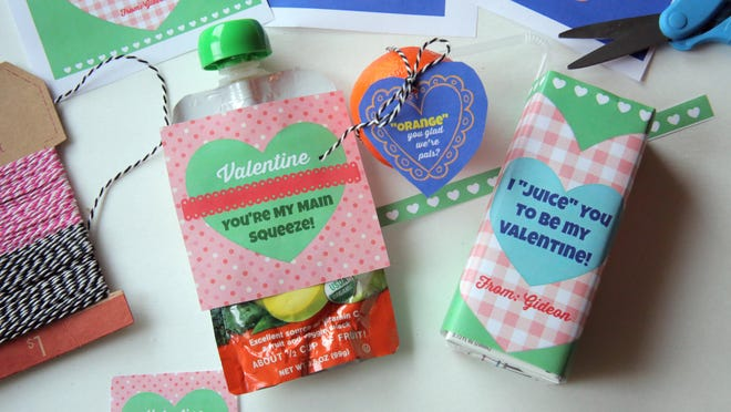An applesauce pouch, tangerine and juice box are converted into Valentine treats.