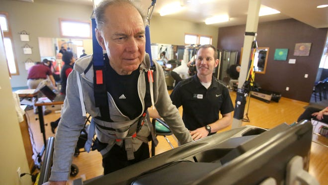 Mel Wiggers (left), a patient at Northwest Rehabilitation Associates, works with physical therapist Mike Studer. Wiggers, who is battling Parkinson's disease, uses a harness on a treadmill that stabilizes him during his treatment.